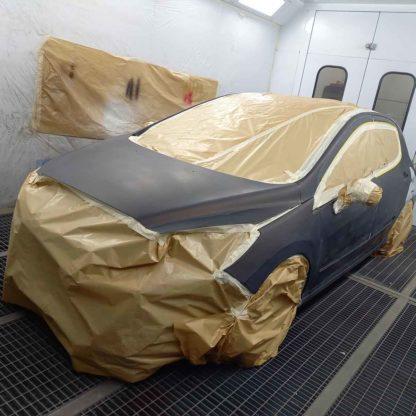 Vue avant d'une voiture peinte dans un atelier de carrosserie avec papier de masquage