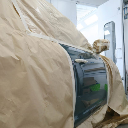 papier de masquage sur une voiture dans un atelier de carrosserie