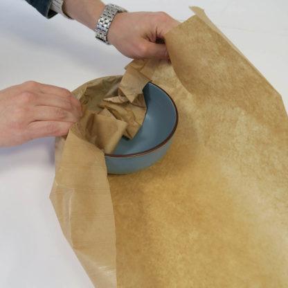 Bol en train d'être emballé avec du papier kraft